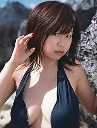 Cute asian babe showing off her tits at the beach in a bikini