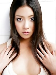 Maki Miyamoto cleavage exposed as she poses in a low cut dress